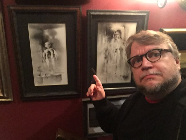 "Guillermo del Toro vor zwei Bildern aus dem Kinderbuch ""Scary Stories to Tell in the Dark"""